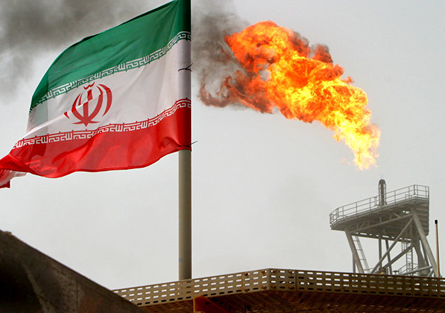 Gas flare on an oil production platform in the Soroush oil fields is seen alongside an Iranian flag in the Gulf July 25, 2005