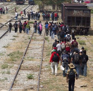 Immigrants walk along the rail tracks after getting off a train during their journey toward the US-Mexico border in Ixtepec, southern Mexico