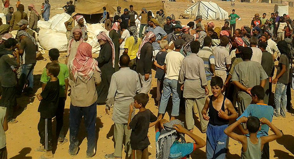 people gather to take basic food stuffs and other aid from community leaders at Rukban refugee camp