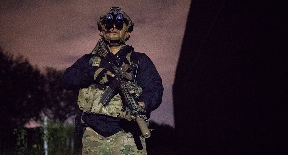 An agent with the U.S. Border Patrol Tactical Unit guards the U.S. side of the border wall with Mexico in Brownsville Texas U.S