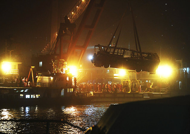 In this Oct. 31, 2018, file photo released by China's Xinhua News Agency, a bus is lifted out of the Yangtze River by a floating crane in Wanzhou in southwestern China's Chongqing Municipality. Police said on Friday, Nov. 2, 2018, a brawl between a passenger and a bus driver was the cause of the bus plunging off a bridge and killing more than a dozen people in southwestern China on Sunday