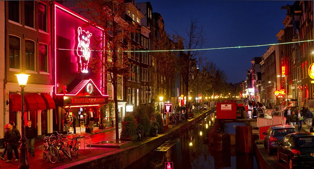 People walk through the red-light district, known as De Wallen, in Amsterdam, on October 13, 2011.