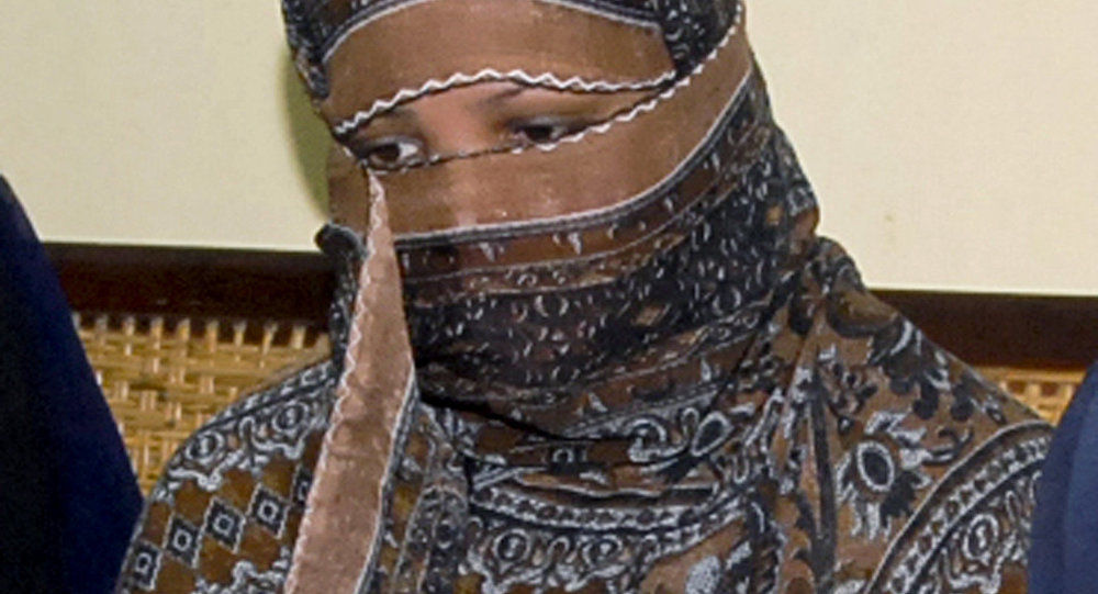 FILE - In this Nov. 20, 2010, file photo, Asia Bibi, a Pakistani Christian woman, listens to officials at a prison in Sheikhupura near Lahore, Pakistan