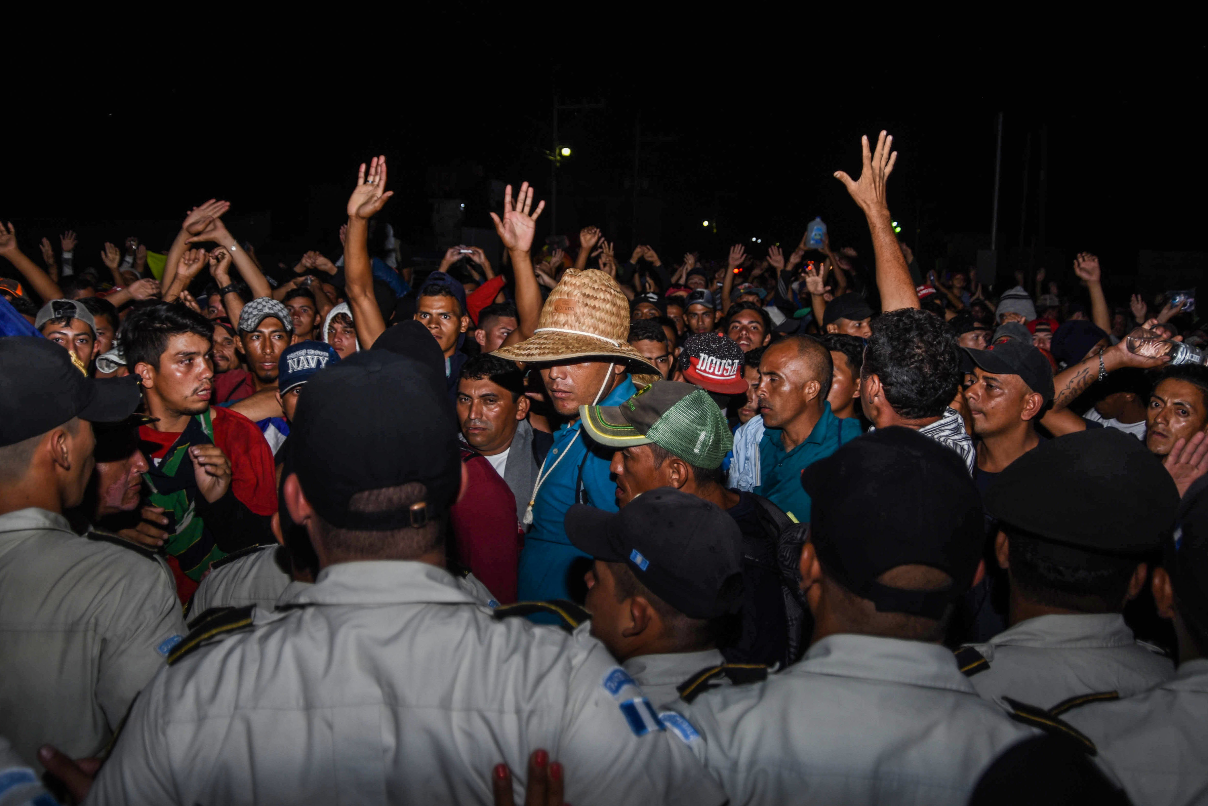 Honduran migrants taking part in a new caravan heading to the US, talk with Guatemalan police officers on their arrival to Chiquimula, Guatemala, on October 22, 2018