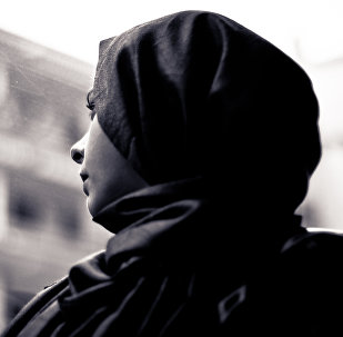 A woman wearing a hijab looks through the window