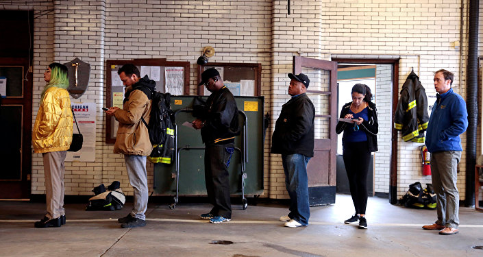 Voters wait to cast their ballots at a fire station serving as a voting place for the midterm election in Detroit