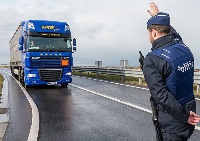 A police man stops a truck on the French-Belgian border in Adinkerke, Belgium, on Wednesday, Feb. 24, 2016.