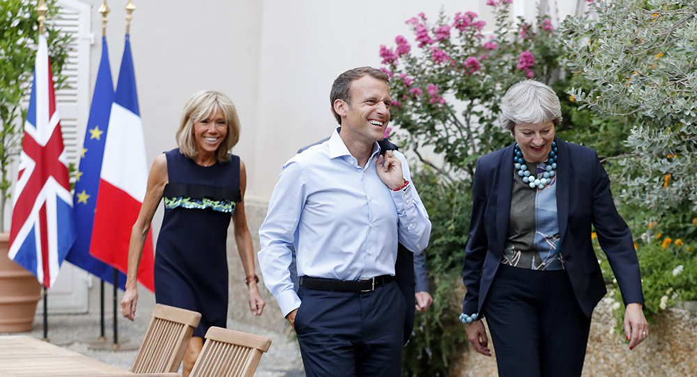 French President Emmanuel Macron and his wife Brigitte Macron, left, walk with British Prime Minister Theresa May, right, and her husband Philip May, hidden, prior to a diner at the Fort de Bregancon in Bornes-les-Mimosas, southern France, Friday Aug. 3, 2018