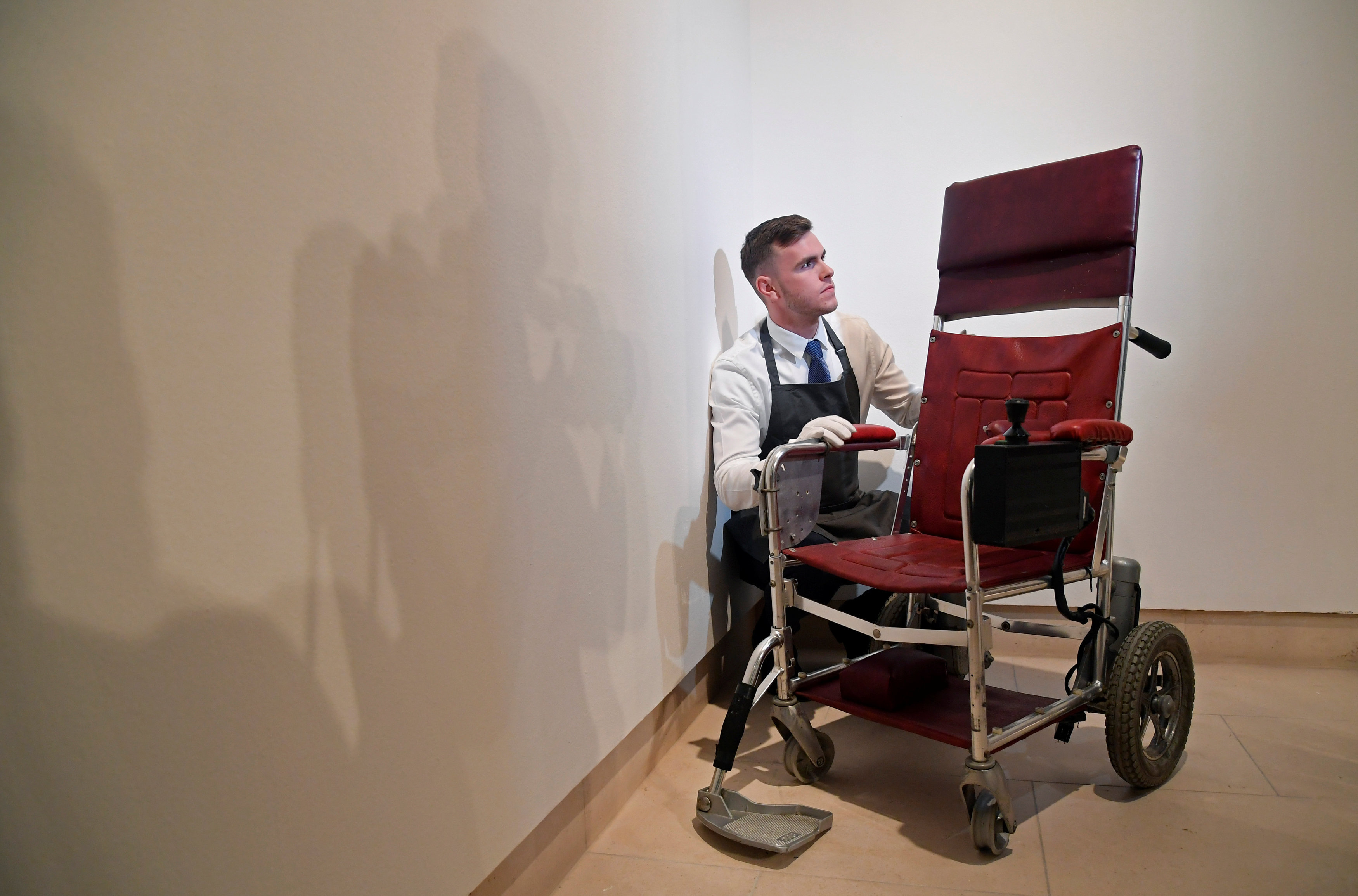 Fine-art handler Tom Richardson poses with a motorised wheelchair belonging to British theoretical physicist Stephen Hawking ahead of an auction of items from Hawkings' personal estate at Christie's in London, Britain October 30, 2018.