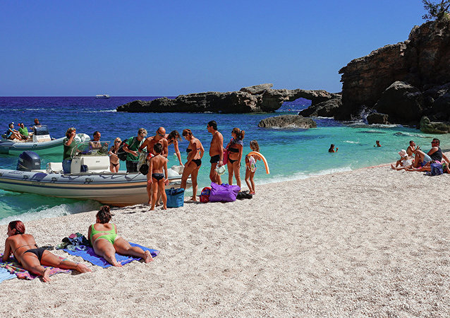 Tourists sunbathing at the beach of Cala Luna, Gulf of Orosei, Sardinia, Italy.