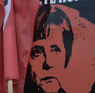 A poster showing German Chancellor Angela Merkel is displayed at a car during a protest against the visit of German Chancellor Angela Merkel at the East German city Chemnitz on Friday, Nov. 16, 2018.