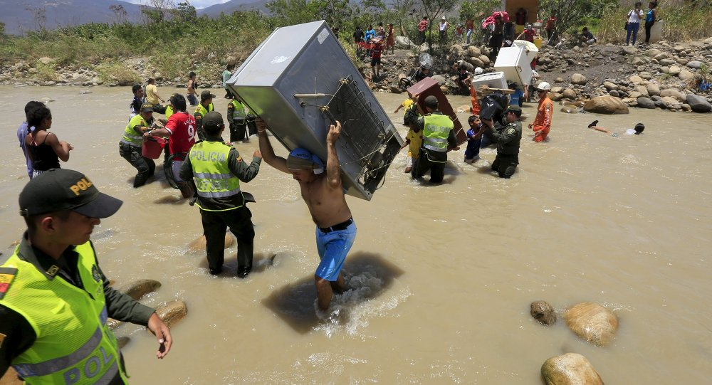 A man carries a refrigerator while crossing the Tachira river border with Venezuela into Colombia, near Villa del Rosario village August 25, 2015