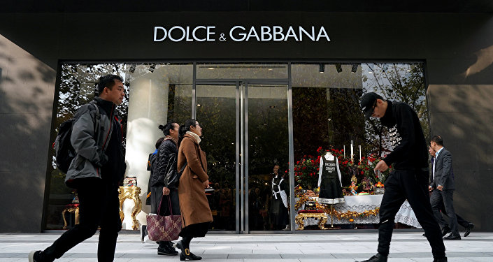 People walk past a Dolce & Gabbana store at a shopping complex in Shanghai, China November 22, 2018