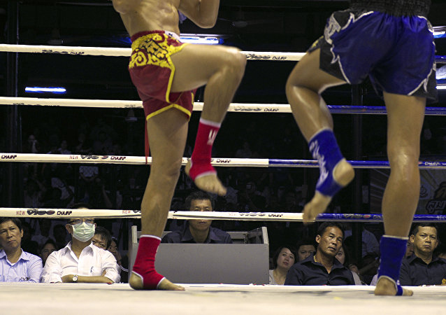 In this Friday, Feb. 7, 2014 photo, veteran judges watch two Muay Thai kick boxers during the last fight night of the famed Lumpinee Boxing Stadium in Bangkok, Thailand