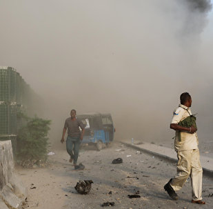 Somali security officers run from the scene of an explosion in Mogadishu