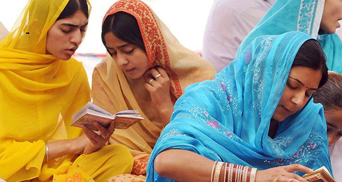 Indian Sikh devotees read the Sikh Holy Book at the Gurdawara Dera Sahibin in Lahore on June 16, 2006.