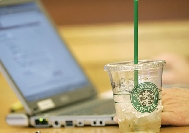 An iced drink sits next to a laptop computer in use Monday, Feb. 11, 2008, at a Starbucks Corp. store near the University of Washington in Seattle. Starbucks and AT&T Inc. will start offering a mix of free and paid wireless Internet service in most of the international coffee retailer's U.S. shops, beginning this spring.