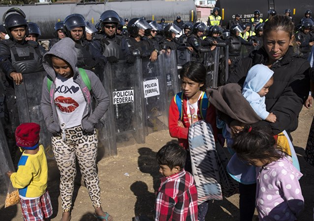 Migrants stand near Mexican police at the Mexico-US border in Tijuana, Mexico, 25 November 2018, as they try to reach the US.