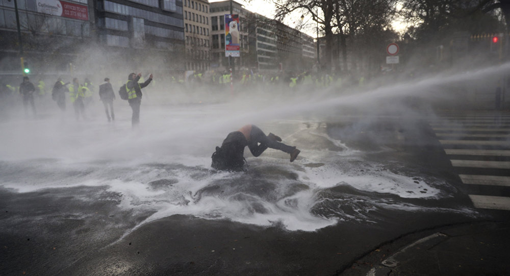 A demonstrator gets hit by a water cannon during a protest of the yellow jackets in Brussels, Friday, Nov. 30, 2018