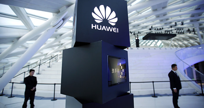 Security personnel stand near a pillar with the Huawei logo