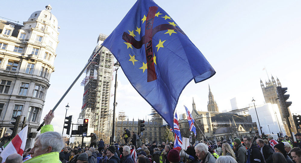 Demonstrators hold placards and flags at the Brexit Betrayal Rally, a pro-Brexit rally, outside the Houses of Parliament in London, Sunday Dec. 9, 2018