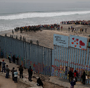 People take part in a gathering in support of the migrant caravan in San Diego, U.S., close to the border wall between the United States and Mexico, as seen from Tijuana, Mexico December 10, 2018