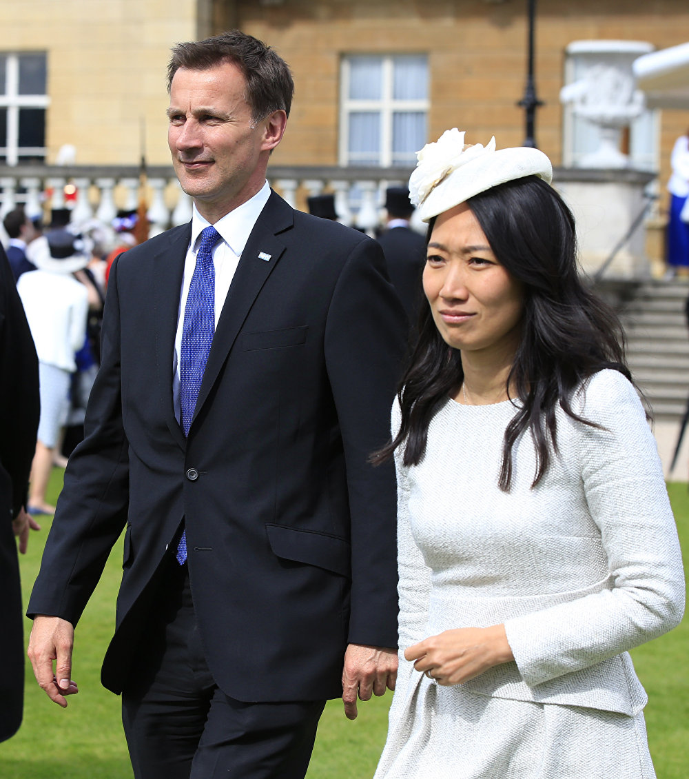 Britain's Health Minister Jeremy Hunt (L) and his wife Lucia, attend a garden party hosted by Britain's Queen Elizabeth II at Buckingham Palace in London on May 19, 2016.