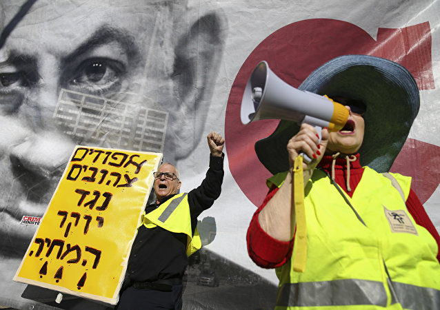 Israelis chant slogans next to a banner showing Israeli Prime Minister Benjamin Netanyahu during a protest against the rising cost of living, in Tel Aviv, Israel, Friday, Dec. 14, 2018. Sign in Hebrew reads Yellow vests against the rising cost of living.