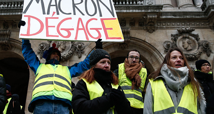 French activist Jean-Baptiste Redde, aka Voltuan, wearing a yellow vest (gilet jaune) holds a cardboard reading Macron go away during a demonstration in front of the Opera House in Paris against rising costs of living blamed on high taxes, on December 15, 2018