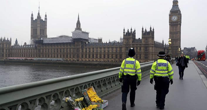 Police officers walk past floral tributes placed at the scene of an attack on Westminster Bridge, in London, Britain March 24, 2017