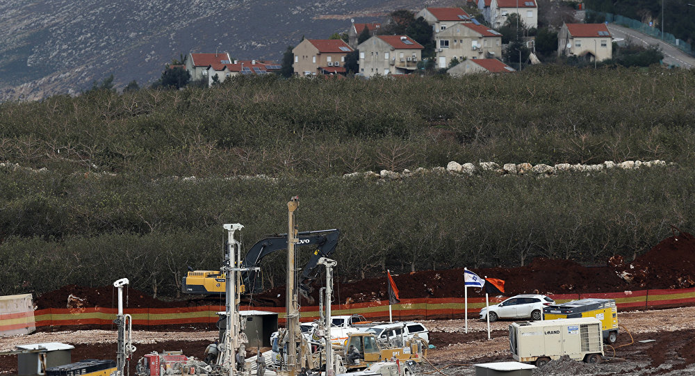 In this Thursday, Dec. 13, 2018 photo, Israeli military equipment works on the Lebanese-Israeli border in front of the Israeli town of Metula, background, near the southern village of Kafr Kila, Lebanon. As Israeli excavators dig into the rocky ground, Lebanese across the frontier gather to watch what Israel calls the Northern Shield operation aimed at destroying attack tunnels built by Hezbollah. But Lebanese soldiers in new camouflaged posts, behind sandbags, or inside abandoned homes underscore the real anxiety that any misstep could lead to a conflagration between the two enemy states that no one seems to want.