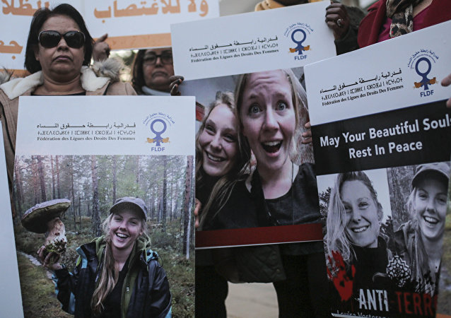 Moroccan women carry photos of 28-year-old Norwegian Maren Ueland and 24-year-old Danish Louisa Vesterager Jespersen, during a candlelight vigil outside the Danish embassy in Rabat for the two Scandinavian university students who were killed in a terrorist attack in a remote area of the Atlas Mountains, Morocco, Saturday, Dec. 22, 2018