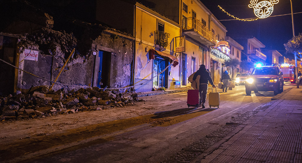 A man carries his belongings as he walks past debris of a partially collapsed house in Fleri Sicily Italy Wednesday Dec. 26 2018