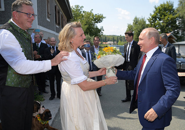 August 18, 2018. Russian President Vladimir Putin gives flowers to Austrian Foreign Minister Karin Kneissl during her wedding to entrepreneur Wolfgang Meilinger, left