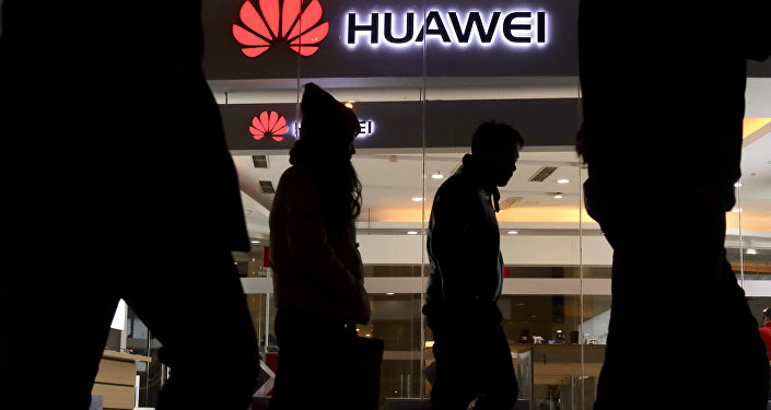 Pedestrians walk past a Huawei retail shop in Beijing Thursday, Dec. 6, 2018