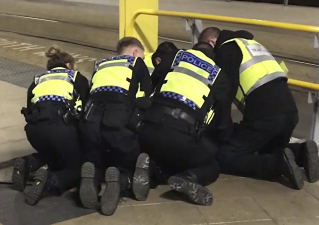 UGC issued by PA shows Police restraining a man after he stabbed three people at Victoria Station in Manchester, England, late Monday Dec. 31, 2018