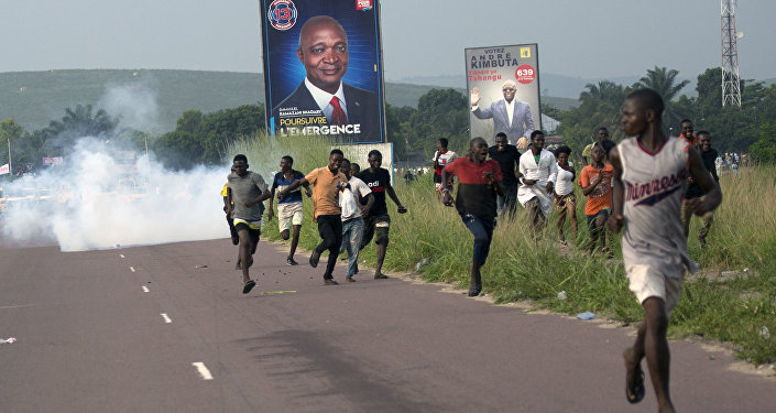 Supporters of opposition candidate Martin Fayulu run from tear gas fired by police in Nsele, Democratic Republic of the Congo, on December 19