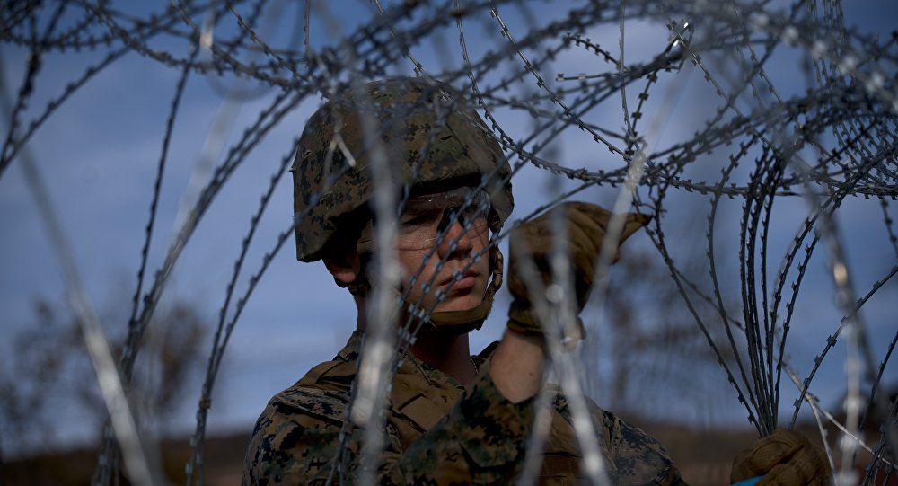 A soldier agent sets up barbed wire at the San Ysidro port of entry, at the U.S.-Mexico border, seen from Tijuana, Mexico, Thursday, Nov. 22, 2018