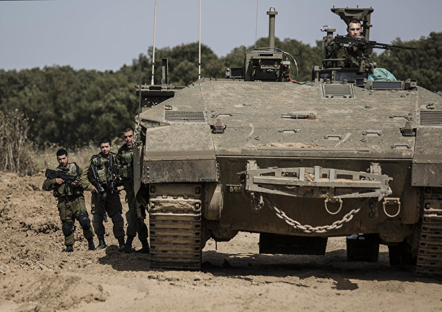 Israeli soldiers stand by a tank near the Israel Gaza border