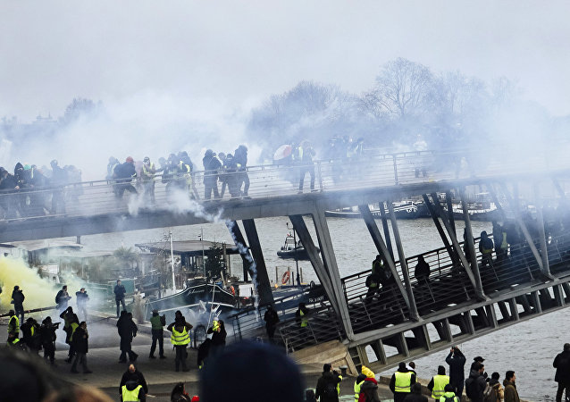 Tear gas is thrown by riot police as demonstrators wearing yellow vests try to cross a pedestrian bridge during march in Paris, Saturday, Jan. 5, 2019.