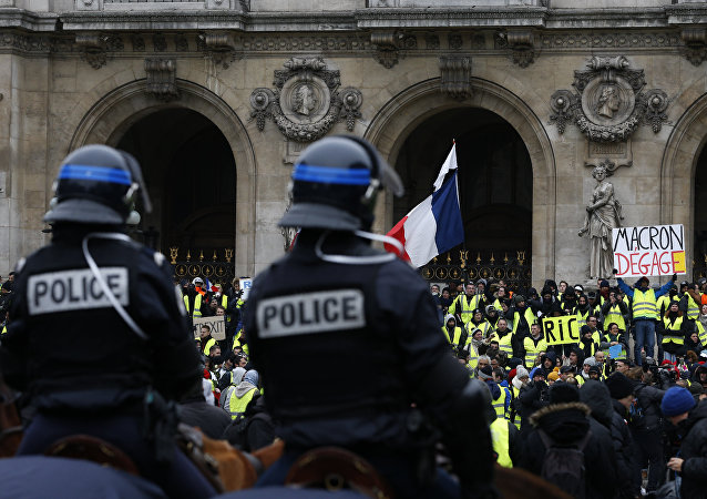 French mounted police stand in front protesters wearing yellow vests