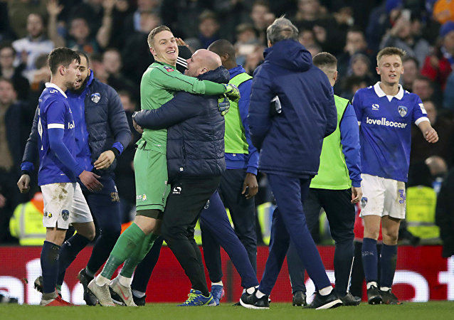 Oldham's caretaker manager Pete Wild embraces the players after victory over Fulham on January 6, 2018