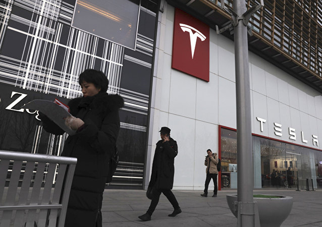 Residents walk past a Tesla store in Beijing