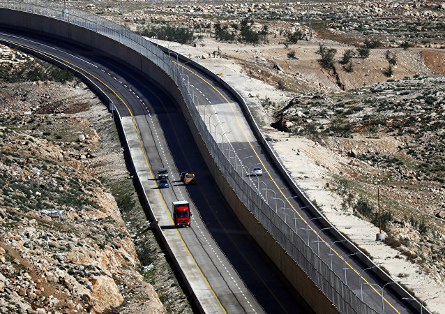 Cars drive on a new Israeli road divided by a wall to separate it for Palestinians (L) and the side to be used exclusively by Israelis and settlers (R) in East Jerusalem, on January 10, 2019