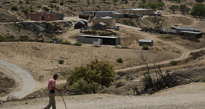 In this May 12, 2015 file photo, a Bedouin man walks through the village of Umm Al-Hiran in the Israeli Negev desert