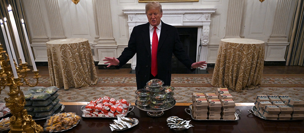 President Donald Trump talks to the media about the table full of fast food in the State Dining Room of the White House in Washington, Monday, Jan. 14, 2019, for the reception for the Clemson Tigers.
