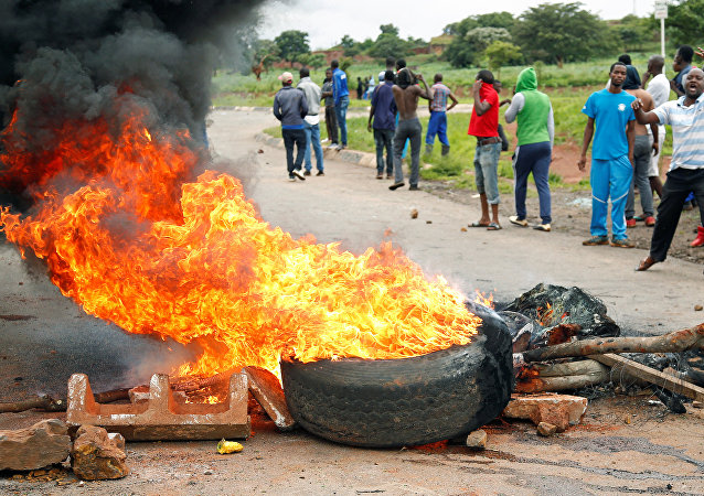 Protesters stand behind a burning barricade during protests on a road leading to Harare, Zimbabwe, January 15, 2019