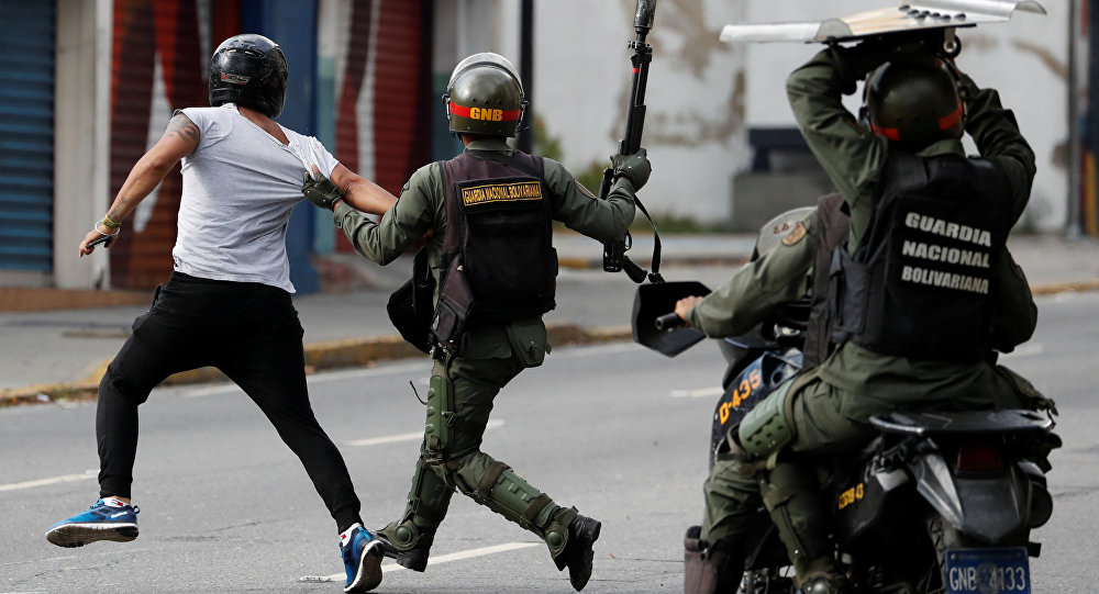 Security forces run after a demonstrator during a protest of opposition supporters against Venezuelan President Nicolas Maduro's government in Caracas, Venezuela