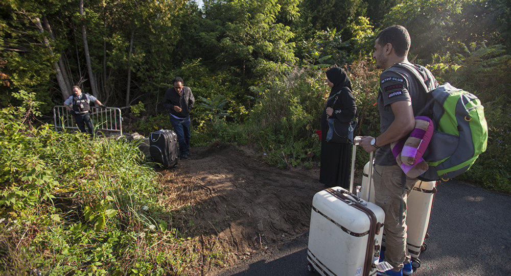 RCMP officers speaks with migrants as they prepare to cross the US/Canada border illegally near Hemmingford, Quebec, August 20, 2017
