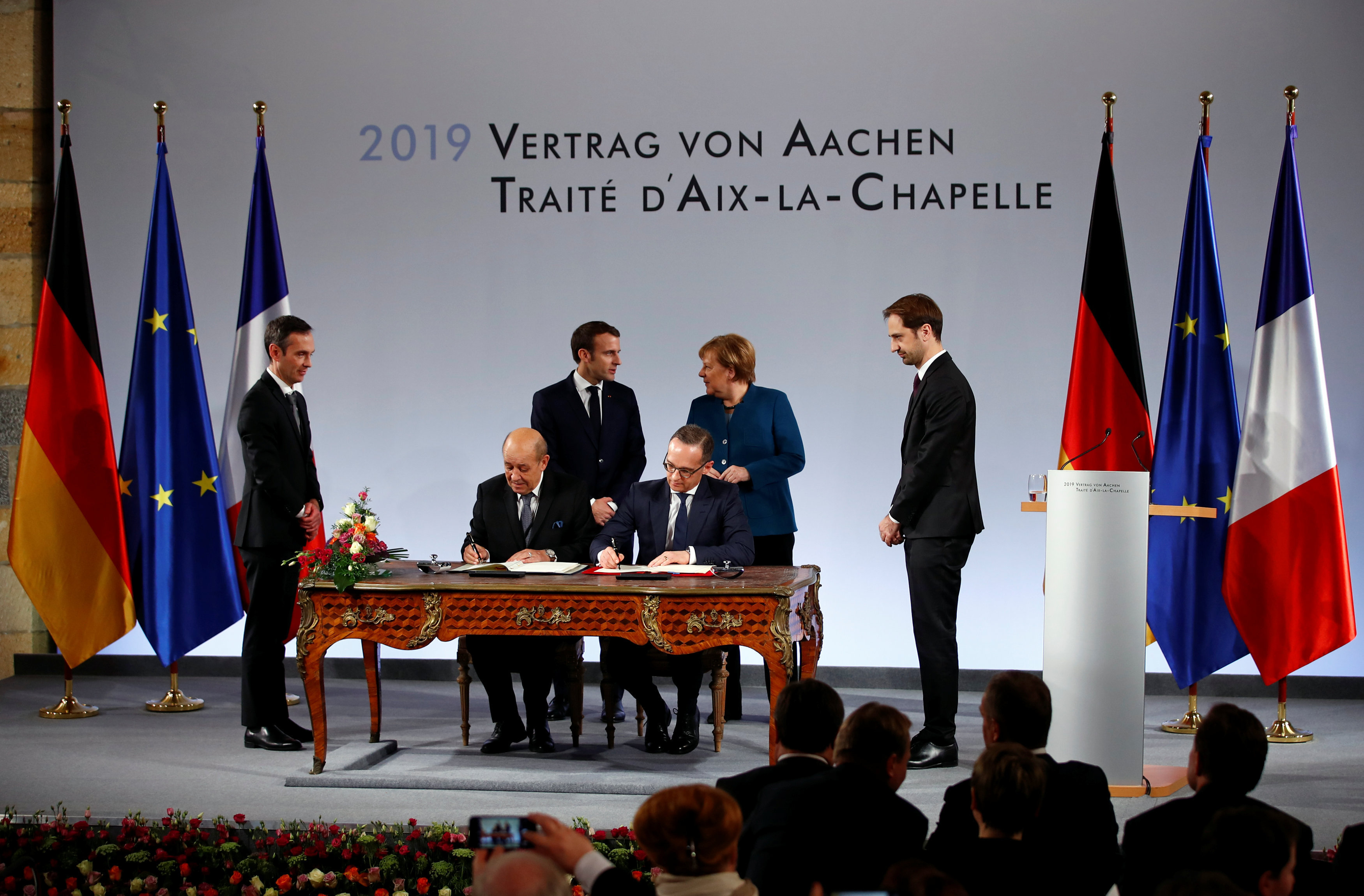 French Foreign Minister Jean-Yves Le Drian and his German counterpart Heiko Maas sign a new agreement on bilateral cooperation and integration, known as Treaty of Aachen, as German Chancellor Angela Merkel and French President Emmanuel Macron look on, in Aachen, Germany, January 22, 2019